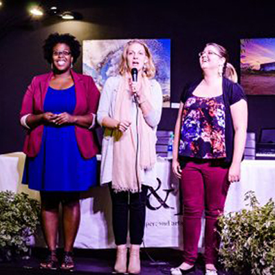 The Fringe Marketing Group of Macon-Branding. Picture of the Lost Keys Collective board smiling on stage, with the founder, Danielle Quesenberry in the center holding a microphone.