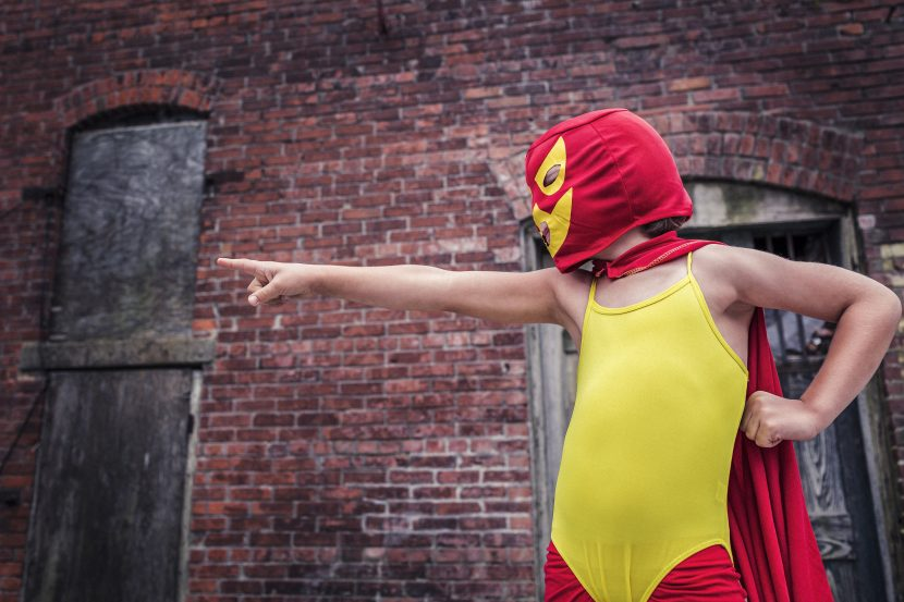 Difference Between Perfection and Greatness. Picture of a young person in a red and yellow superhero costume, pointing their finger.